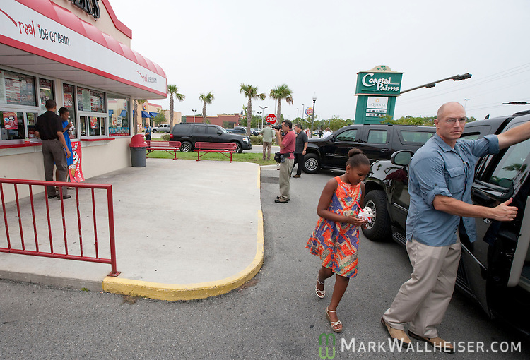PANAMA CITY BEACH, FL -  AUGUST 15:  President Barack Obama and First Lady Michelle eat their ice cream in front of Bruster's Real Ice Cream while 9 year-old daughter Sasha heads to the car August 15, 2010 in Panama City Beach, Florida.  The Obamas are vacationing in the Florida panhandle.