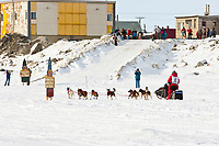 Rookie musher Jane Faulkner runs past Nome welcome signs on the seawall ice nearing the finish line in Nome during the 2010 Iditarod