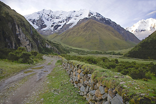 AN OLD ROAD AND ROCK WALL LEAD THE WAY TO THE SALKANTAY PASS IN THE PERUVIAN ANDES.