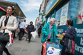 Elderly shoppers chat outside a Poundland store, Kilburn, London.