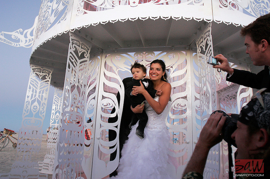 BLACK ROCK CITY, NV - AUGUST 27,2008:  A wedding in the desert. Mercedes Martinez and her son Sebastian, 18 months, after a wedding on the Playa. Mercedes Martinez and Chris Weitz held a wedding ceremony with friends gathered at Burning Man Event 2008. Participants from around the world converge in Nevada for the annual art event. The event, which culminates with the burning of large installation art over the weekend, attracts over 30,000 people annually.