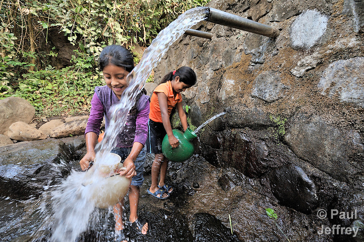 Girls get water from a community water source in Santa Catarina Masahuat, El Salvador.