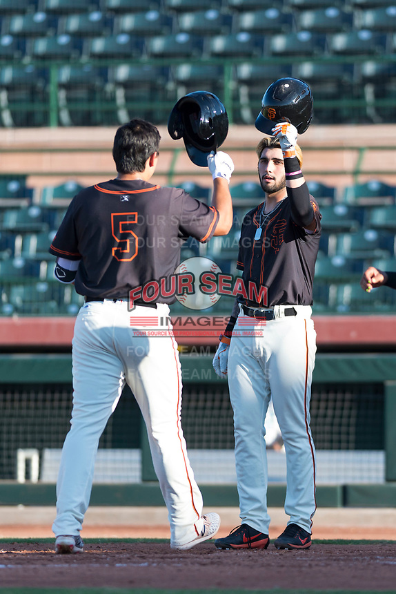 AZL Giants Orange first baseman Frankie Tostado (10) congratulates Sean Roby (5) for hitting a home run during an Arizona League game against the AZL Rangers at Scottsdale Stadium on August 4, 2018 in Scottsdale, Arizona. The AZL Giants Black defeated the AZL Rangers by a score of 3-2 in the first game of a doubleheader. (Zachary Lucy/Four Seam Images)