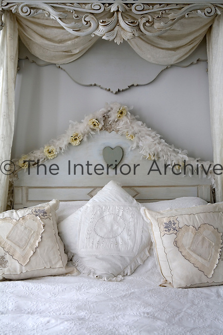 Detail of the carved wooden half-tester bed with pretty cushions and a white bed cover