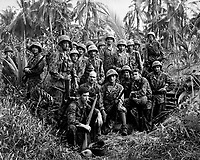 These men have earned the bloody reputation of being skillful jungle fighters.  They are U.S. Marine Raiders gathered in front of a Jap dugout on Cape Totkina on Bougainville, Soloman Islands, which they helped to take.  January 1944. (Navy)<br /> Exact Date Shot Unknown<br /> NARA FILE #: 080-G-205686<br /> WAR &amp; CONFLICT BOOK #:  1200