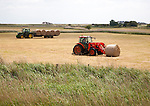 Tractor and trailer collecting round straw bales, Oxley marshes, Hollesley, Suffolk, England, UK