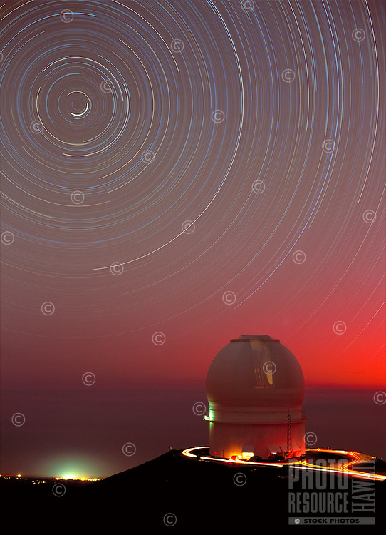 Star trails over the Canada-France-Hawaii Telescope, Mauna Kea Observatory, Hawaii.  The arcs are the paths followed by stars as they move across the sky due to the Earth's rotation.  The North celestial pole is at the center of the arcs, and Polaris is the short bright arc near the center or rotation.