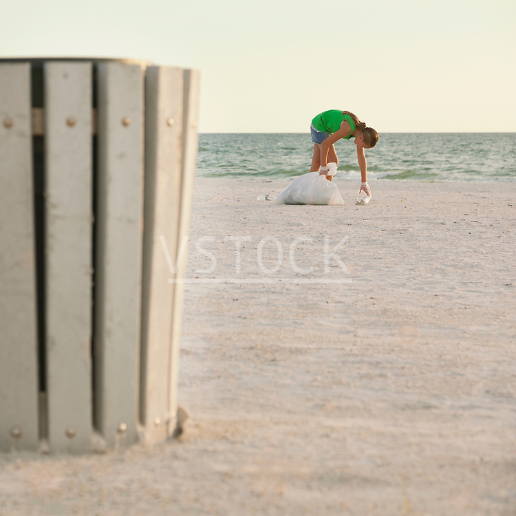 USA, Florida, St. Petersburg, Girl (10-11) cleaning beach, garbage bin in foreground