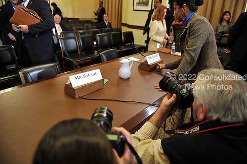 "Washington, D.C. - December 3, 2009 -- Photographers look on as an unidentified staff member prepares the witness table for Tariq and Michaele Salahi at the U.S. House Homeland Security Committee in Washington, D.C. on Thursday, December 3, 2009.  The theme of the hearing was ""The U.S. Secret Service and Presidential Protection: An Examination of a System Failure"".  The committee earlier heard testimony concerning the security lapse at the White House that allowed the Salahis to attend the State Dinner in honor of Prime Minister Singh of India without having been invited.  .Credit: Ron Sachs / CNP.(RESTRICTION: NO New York or New Jersey Newspapers or newspapers within a 75 mile radius of New York City)"