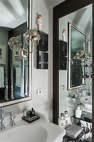The bathroom has a monochrome theme and an inset floor to ceiling mirrored cupboard creates a sense of space.