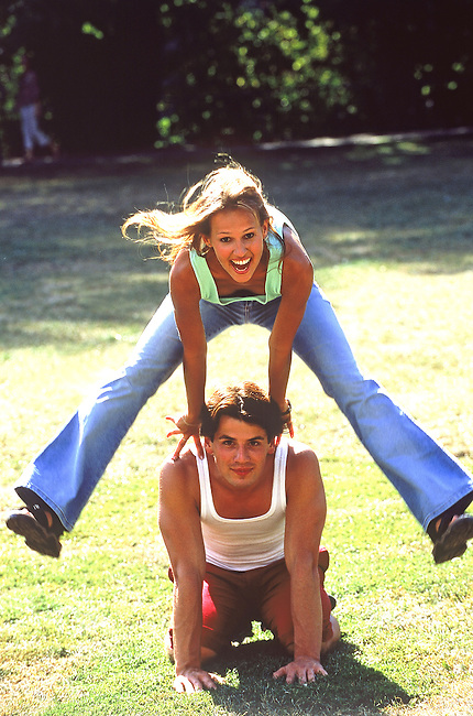 Un couple s'amusant a saute-mouton dans un parc. *** A couple playing leap-frog in a park.