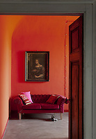 A velvet sofa in a contrasting red creates a vibrant corner in this red painted bedroom