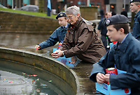 Pictured: A woman places a poppy in the fountain. Saturday November 2017<br />Re: Armistice Day, two minutes were observed to mark remembrance at Castle Square in Swansea, Wales, UK.