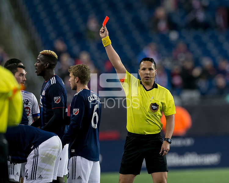 Foxborough, Massachusetts - April 6, 2018: First half action. In a Major League Soccer (MLS) match, New England Revolution (blue/white) vs Montreal Impact (white), at Gillette Stadium.<br /> Red card to Montreal Impact.