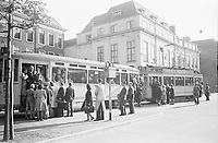 Photo from the NIOD's Huizinga collection. A crowded tram with passengers hanging outside rides through the streets of The Hague.