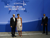 Pittsburgh, PA - September 24, 2009 -- United States President Barack Obama (R) stands by as first lady Michelle Obama is photographed with Minister for Finance of Singapore Tharman  Shanmugaratnam (L) as they arrive to the welcoming dinner for G-20 leaders at the Phipps Conservatory on Thursday, September 24, 2009 in Pittsburgh, Pennsylvania. Heads of state from the world's leading economic powers arrived today for the two-day G-20 summit held at the David L. Lawrence Convention Center aimed at promoting economic growth. .Credit: Win McNamee / Pool via CNP