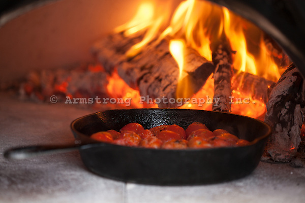 Cherry tomatoes in a cast iron pan with salt and pepper, inside a wood burning oven with burning logs behind it.