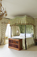 A matching fabric has been used for the walls and curtains of this bedroom. At the foot of the bed is a chest with a veneer of carved books