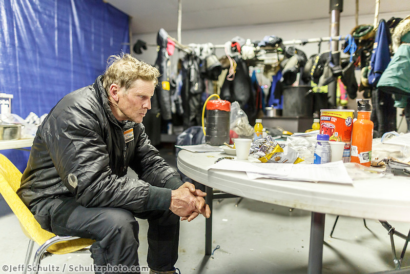 Lachlan Clarke has the 1,000 - mile stare as he rests in the community center as musher gear dries in the backgroud at the Tanana checkpoint on Wednesday morning  March 11th during the 2015 Iditarod.<br /> <br /> (C) Jeff Schultz/SchultzPhoto.com - ALL RIGHTS RESERVED<br />  DUPLICATION  PROHIBITED  WITHOUT  PERMISSION