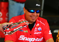 Jun 11, 2016; Englishtown, NJ, USA; NHRA funny car driver Cruz Pedregon autographs a diecast replica during qualifying for the Summernationals at Old Bridge Township Raceway Park. Mandatory Credit: Mark J. Rebilas-USA TODAY Sports