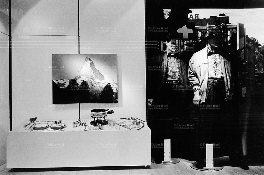Switzerland. Zürich. At a shop's window are displayed a poster of the Matterhorn (Cervin) mountain, a set of plates and pant for the cheese fondue, two mannequins with men's fashion, and a swiss flag.  © 1990 Didier Ruef..