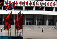 "People pass a Government building in Pyongyang, North Korea. The DPRK (Democratic People's Republic of Korea) is the last great dictatorship where the people are bombarded with images of the ""Eternal President"" Kim Il-sung who died in 1994 and his son and current leader Kim Jong-il who are worshipped like a God."