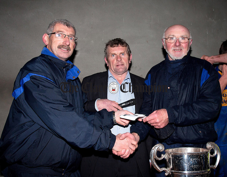 The Clare Champions Liam Duggan (left) presents Tommy Moloney (right), Clonlara, with the runners up cheque after the game at Sixmilebridge on Sunday also pictured is Joe Cooney (centre) who presented the cup to Newmarket Captain Enda Barrett.