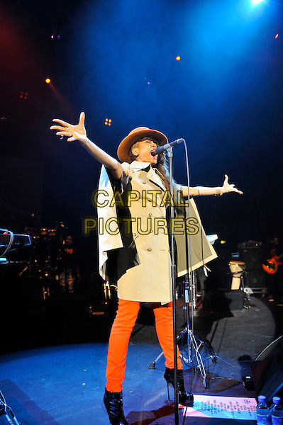 Erykah Badu performing live in concert, Hammersmith Apollo, London, England. 27th June 2012.on stage gig performance full length beige mac orange jeans denim cape hat  singing hands arms boots black.CAP/MAR.© Martin Harris/Capital Pictures.