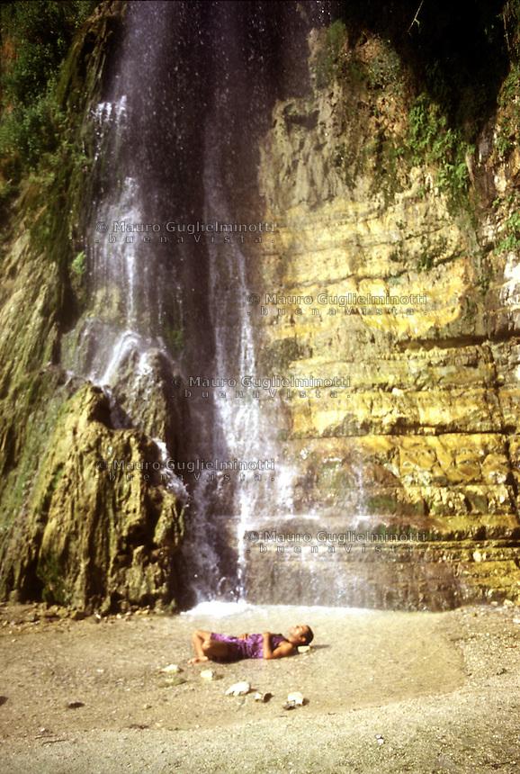 Israele: le cascate di David nella riserva naturale di EIn Gedi sulla costa del Mar Morto. Un turista sdraiato sulla spiaggia sotto la cascata.