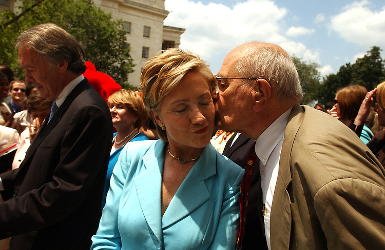 Sen. Hillary Clinton, D-N.Y., gets a kiss from Rep. John Dingell, D-Mich., at a rally on the Cannon Terrace to protect the public radio and television from $100 million of funding cuts proposed for the Corporation for Public Broadcasting.  Rep. Ed Markey, D-Mass., appears at left.