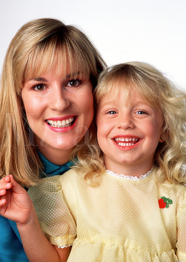 Portrait of a smiling blonde mother and daughter.