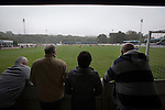 Home team supporters watching the first-half action at the Harry Williams Riverside Stadium, home to Ramsbottom United as they played Barwell in a Northern Premier League premier division match. This was the club's 13th league game of the season and they were still to record their first victory following a 3-1 defeat, watched by a crowd of 176. Rams bottom United were formed by Harry Williams, the current chairman, in 1966 and progressed from local amateur football  in Bury to the semi-professional leagues.
