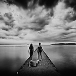 Male and female youths wearing wetsuits standing on a concrete jetty looking out to water with belly boards