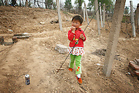 A young child stands in a field in Hebei Province, China. Desertification is the process by which fertile land becomes desert, typically as a result of drought, deforestation, or inappropriate agriculture. 41 % of China's landmass in classified as arid or desert. Inappropriate farming methods and over cultivation have contributed to the spreading of deserts in China in recent years.