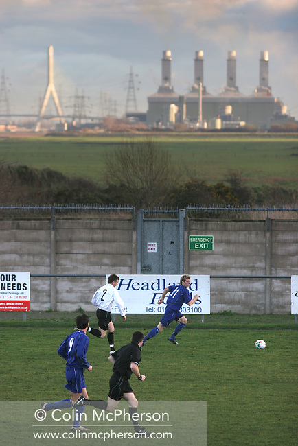 The Flint power station and bridge into England dominating the skyline as Connah's Quay Nomads take on Haverfordwest County (blue shirts) in a Welsh Premier League match at Flint, north Wales. Connah's Quay spent the 2006-07 season groundsharing with Flint United as they redeveloped their own home stadium, located less than five miles along the north Wales coast. The home team won the match by five goals to three, having lead 4-0 after 30 minutes and clinching the victory with their fifth goal six minutes from time.