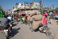 Street scene at Daryagang as porter carries produce by bicycle in Old Delhi, India