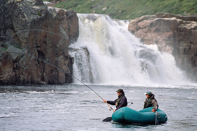 A salmon angler with his guide fly fishing in the Falls Pool on the Eastern Litza River. Kola Peninsula, NW Russia.