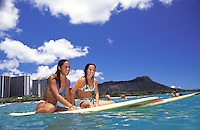 Two local teenage girls on surfboards at Waikiki beach with Diamond head in rear