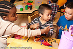 Education preschool 3-4 year olds group of two boys and a girl in kitchen area pretend play with food talking discussion horizontal