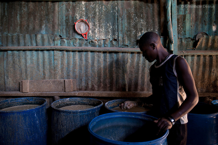 James Watoya checks the fermentation of the Busaa, a traditional fermented beer, at the Madiaba Busaa Club in a Nairobi slum on March 27, 2013. Busaa is made by crudely fermenting maize, millet, sorghum or molasses. At Kshs 35 per liter it is much cheaper than a Kshs120 half-liter bottle of commercial beer. The local brew was legalised in 2010 and since then busaa clubs have become increasingly popular. Drinking is on the rise in Kenya, especially among young people. Photo: Benedicte Desrus