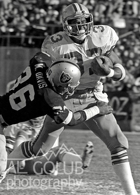 Oakland Raiders vs Dallas Cowboys at Oakland-Alameda County Coliseum Sunday, December 7, 1980.Oakland Raider Defensive Back Mike Davis (36) tackles Dallas Cowboys Running Back Tony Dorsett (33)..Raiders lost to the Cowboys 13 -19, but they did will the Superbowl in post season.