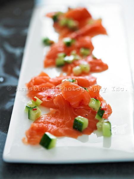 Salmon lox on a long plate with diced cucumber and drizzled with olive oil