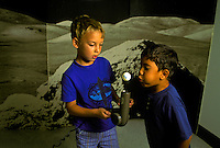 Two children experiment with concept of anti-gravity, using ping-pong ball and hair dryer, in front of moonscape background at science center