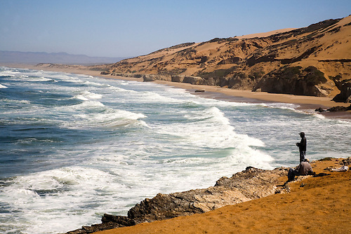 FISHERMAN AT GUADALUPE BEACH AND SAND DUNES, PACIFIC OCEAN, CALIFORNIA