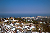 Village of Mijas in foreground (church tower at left center, bullring immediately below that) Fuengirola on the Costa del Sol and the Mediterranean in distance. Mijas Andalucia Spain Costa del Sol.