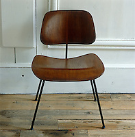 A simple Charles Eames chair is placed against 19th century French wood panelling