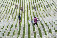 NEW YORK, NY - MAY 25: View of a man and a woman along with two children walking among the graves of American soldiers at the Cypress Hill Military Cemetery on May 25, 2020 in Brooklyn, NY. Memorial Day is an American holiday that commemorates the men and women who died while serving in the United States Army. Today this date is celebrated during the Covid-19 pandemic that has caused thousands of deaths in the United States and around the world.  (Photo by Pablo Monsalve / VIEWpress)