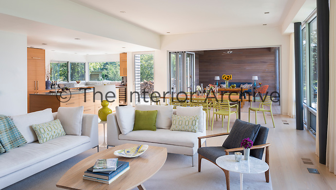 A modern, spacious open plan room with sitting, dining and kitchen areas. Two light grey sofas and two grey armchairs are grouped around a coffee table. A dining table and chairs are placed in one half of the room. Acid green is used as an accent colour around the room.