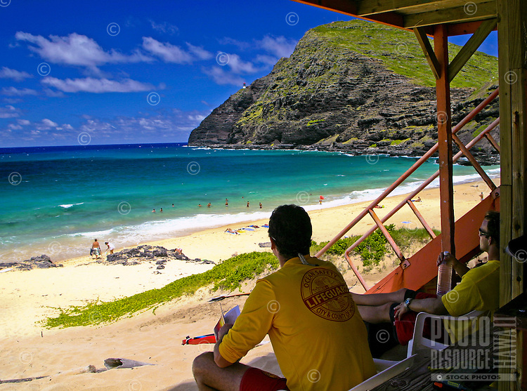 A life gaurd stands watch over beautiful Makapuu Beach. A popular beach for swimming and body boarding. East coast of Oahu.
