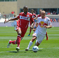 Chicago defender Cory Gibbs (5) plays the ball in front of New York midfielder Joel Lindpere (20).  The Chicago Fire tied the New York Red Bulls 1-1 at Toyota Park in Bridgeview, IL on June 26, 2011.
